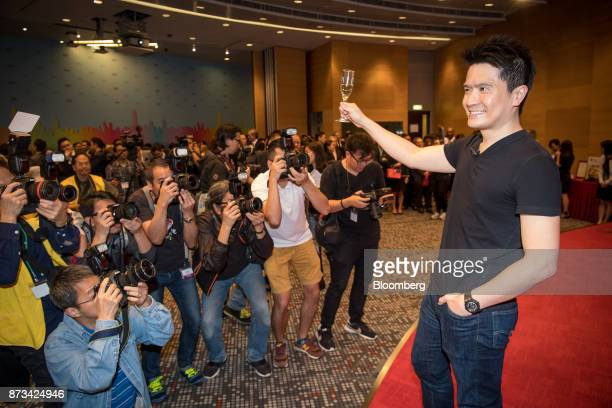 Billionaire Tan Min-Liang, chief executive officer and co-founder of Razer Inc., raises a champagne glass as he stands for photographs for members of...