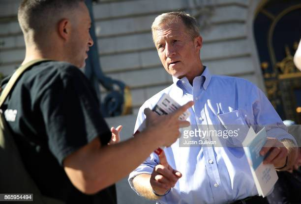 Billionaire Tom Steyer greets an attendee during a rally and press conference at San Francisco City Hall on October 24 2017 in San Francisco...