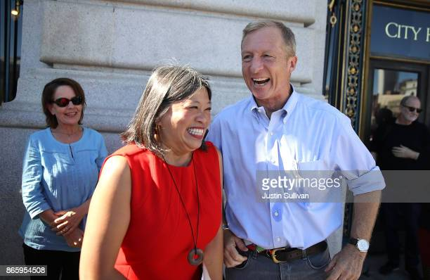 Billionaire Tom Steyer laughs with San Francisco supervisor Sandra Lee Fewer during a rally and press conference at San Francisco City Hall on...