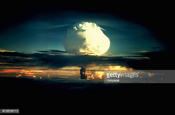 A billowing white mushroom cloud mottled with orange pushes through a layer of clouds during Operation Ivy the first test of a hydrogen bomb at...