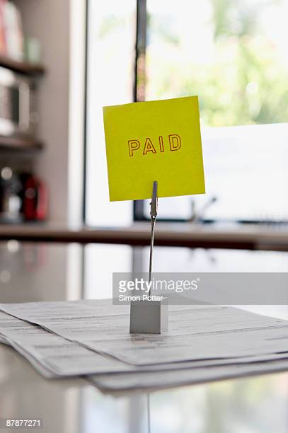 bills on a paid pile - paid stock pictures, royalty-free photos & images