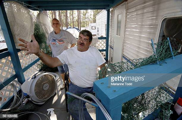 Billy Arceneaux of Biloxi makes fishing nets from his FEMA trailer in a park as his friend Janyce Carter looks on November 14 2005 in Kiln...