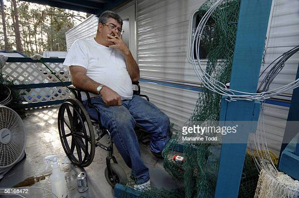 Billy Arceneaux of Biloxi smokes a cigarette while making fishing nets from his FEMA trailer in a park November 14 2005 in Kiln Mississippi Arceneaux...