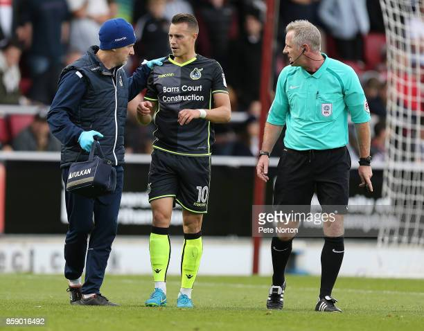 Billy Bodin of Bristol Rovers is helped from the pitch after sustaining an injury whilst scoring his sides first goal as referee Mark Heywood looks...