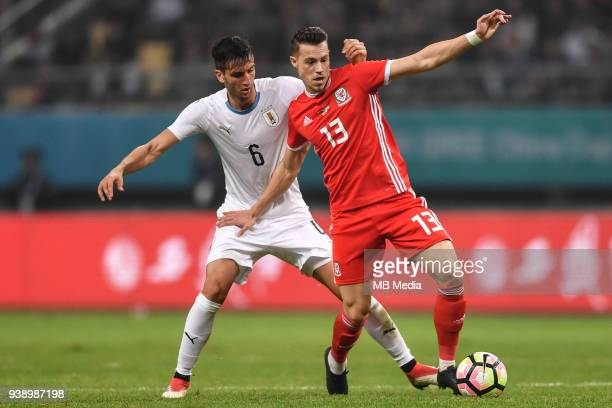 Billy Bodin right of Wales national football team kicks the ball to make a pass against Rodrigo Bentancur of Uruguay national football team in their...
