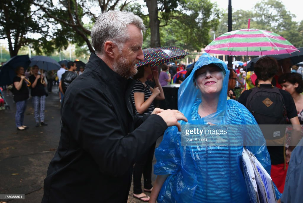 Billy Bragg helps a fellow protester with her poncho during a protest demonstration against the Abbott led Coalition Government on March 16, 2014 in Sydney, Australia. March In March is a nationwide grassroots protest organized to deliver a statement of no confidence in the current Australian Government.