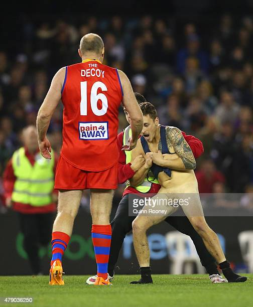 Billy Brownless of the All Stars looks on as a streaker is taken away by security during the EJ Whitten Legends Game at Etihad Stadium on June 30...