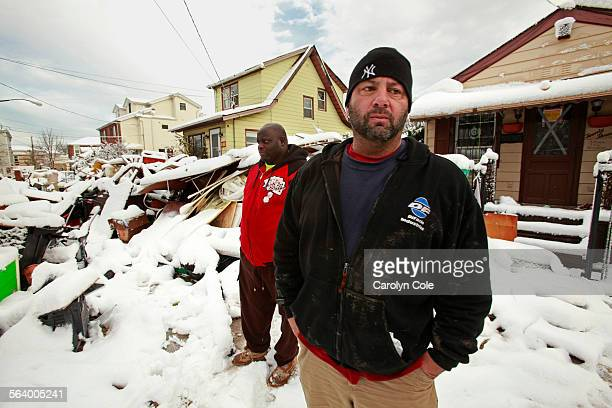 Billy Burke right had his basement flooded on Staten Island and his home is still without electricity He and Travis Harrell left are working to move...