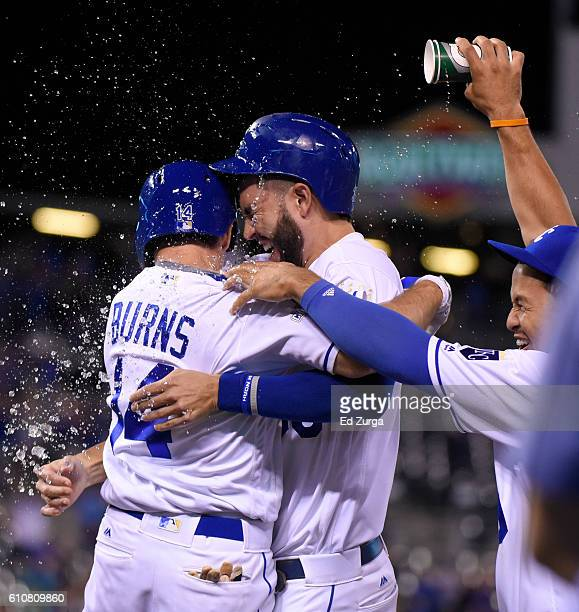 Billy Burns and Eric Hosmer of the Kansas City Royals are doused with water by Cheslor Cuthbert after Burns' sacrifice fly gave the Royals a 43 win...