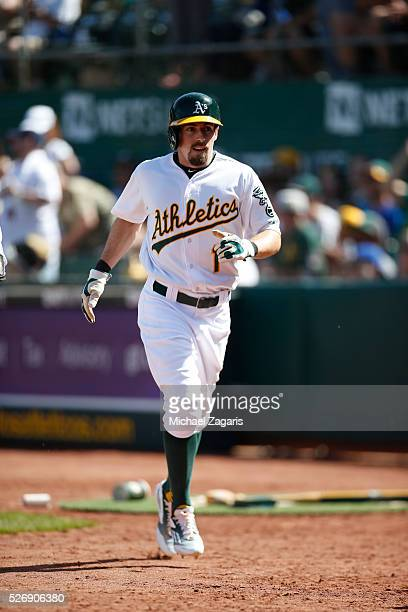Billy Burns of the Oakland Athletics heads to the dugout after scoring during the game against the Kansas City Royals at the Oakland Coliseum on...