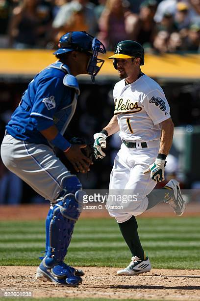 Billy Burns of the Oakland Athletics scores a run past Salvador Perez of the Kansas City Royals during the eighth inning at the Oakland Coliseum on...