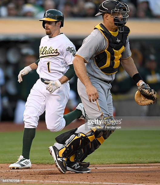 Billy Burns of the Oakland Athletics scores running past Erik Kratz of the Pittsburgh Pirates in the bottom of the third inning at Oco Coliseum on...