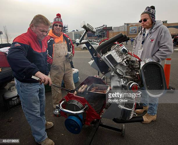 Billy Burrows of Billerica grills on a Chevy 327 engine block for his friends Kevin Callahan center and Fred MacLeod in the parking lot before the...