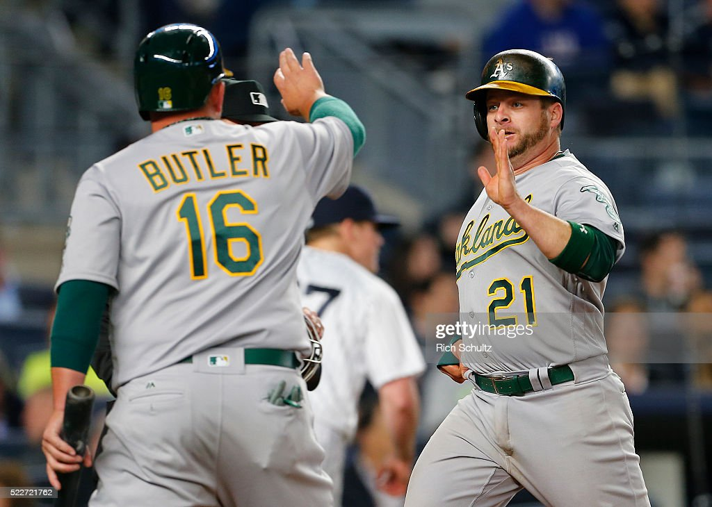 Billy Butler #16 congratulates Stephen Vogt #21 of the Oakland Athletics after scoring on a single by Khris Davis #2 in eighth inning against the New York Yankees at Yankee Stadium on April 20, 2016 in the Bronx borough of New York City. The A's defeated the Yankees 5-2.