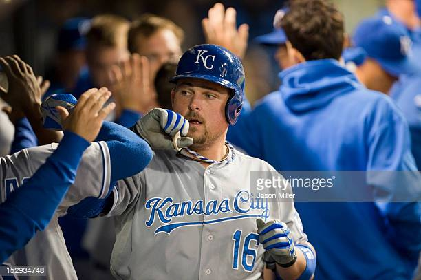 Billy Butler of the Kansas City Royals celebrates in the dugout after hitting a tworun home run in the sixth inning against the Cleveland Indians at...