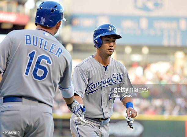 Billy Butler of the Kansas City Royals slaps hands with Norichika Aoki after Aoki scored on an RBI single hit by Eric Hosmer during the first inning...
