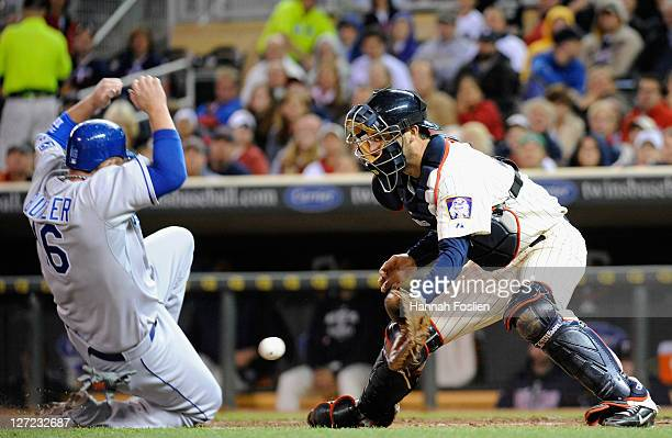 Billy Butler of the Kansas City Royals slides safely as Drew Butera of the Minnesota Twins defends home plate in the sixth inning on September 26...