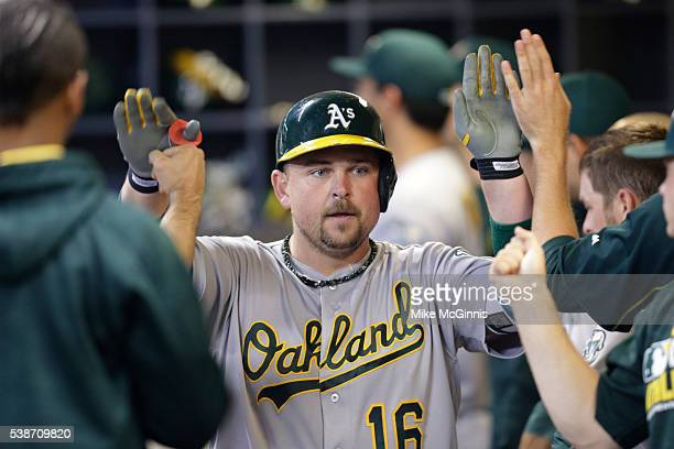 Billy Butler of the Oakland Athletics celebrates in the dugout after hitting a two run homer during the seventh inning of the Interleague game...