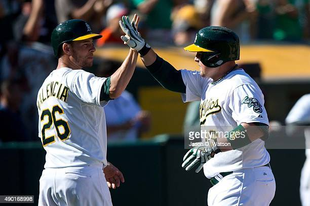 Billy Butler of the Oakland Athletics is congratulated by Danny Valencia after hitting a two run home run against the San Francisco Giants during the...
