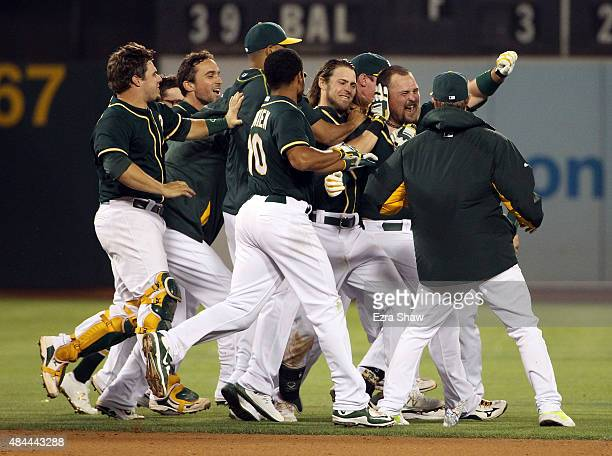 Billy Butler of the Oakland Athletics is surrounded by teammates after he hit in the winning run against the Los Angeles Dodgers in the tenth inning...