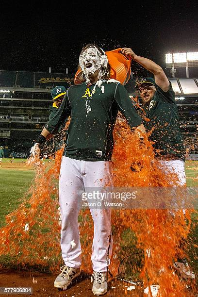 Billy Butler of the Oakland Athletics pours Gatorade on Josh Reddick after Reddick hit a walk off single against the Houston Astros during the tenth...