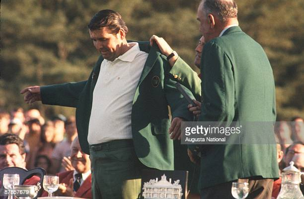 Billy Casper helps Masters Champion Charles Coody speaks with his Green Jacket at the Presentation Ceremony during the 1971 Masters Tournament at...