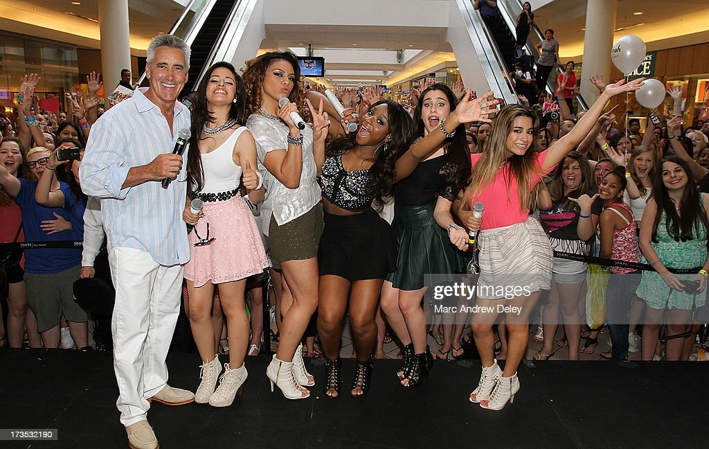 Billy Costa from Kiss 108 FM joins Fifth Harmony on stage after their performance at the Square One Mall on July 15, 2013 in Saugus, Massachusetts.