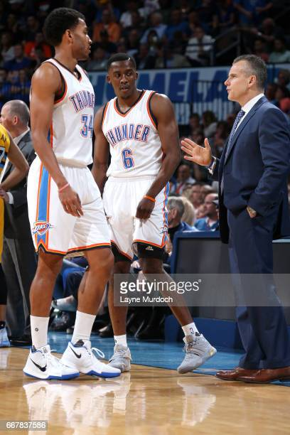 Billy Donovan of the Oklahoma City Thunder talks with Josh Huestis and Semaj Christon of the Oklahoma City Thunder during the game against the Denver...