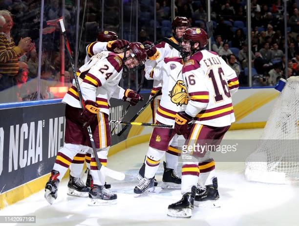 Billy Exell of the MinnesotaDuluth Bulldogs celebrates his goal with teammates Mikey Anderson Dylan Samberg in the third period against the...
