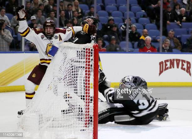 Billy Exell of the MinnesotaDuluth Bulldogs scores a goal as Hayden Hawkey of the Providence Friars reacts in the third period during the semifinals...
