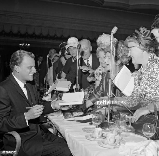 Billy Graham signs copies of his book 'World Aflame' at Foyles Literacy Luncheon held in the Dorchester Ballroom. The event was held in his honour,...