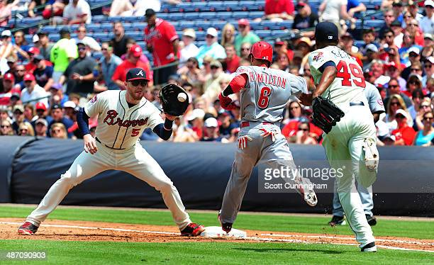 Billy Hamilton of the Cincinnati Reds beats out an infield hit during the 3rd inning against Freddie Freeman and Julio Teheran of the Atlanta Braves...