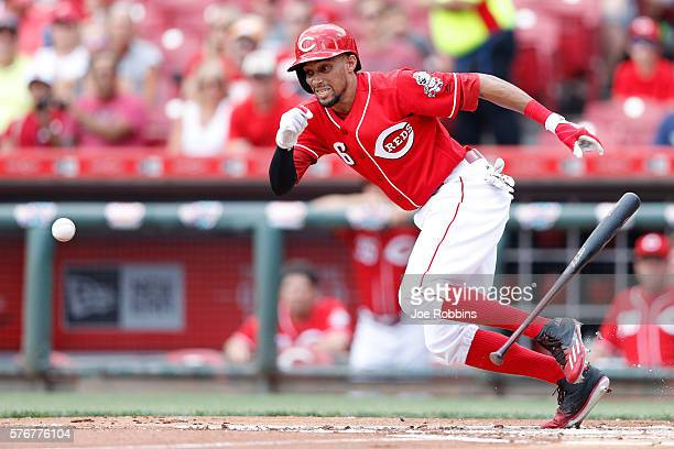 Billy Hamilton of the Cincinnati Reds bunts for a single in the first inning against the Milwaukee Brewers at Great American Ball Park on July 17...