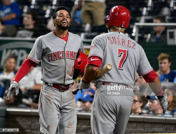 Billy Hamilton of the Cincinnati Reds celebrates with Eugenio Suarez after scoring on a Joey Votto threerun triple in the 10th inning against the...