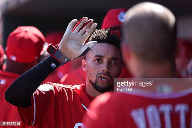 Billy Hamilton of the Cincinnati Reds celebrates with teammates in the dugout after scoring a run during the first inning of a spring training game...