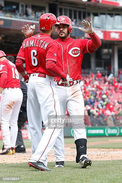 Billy Hamilton of the Cincinnati Reds congratulates Eugenio Suarez of the Cincinnati Reds after hitting a two run home run in the bottom of the...