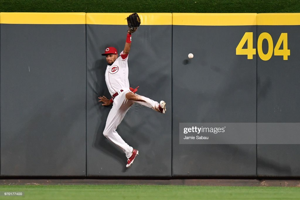 Billy Hamilton #6 of the Cincinnati Reds crashes in to the center field wall as he chases down a ball hit for a triple by Marcell Ozuna #23 of the St. Louis Cardinals in the eighth inning at Great American Ball Park on June 8, 2018 in Cincinnati, Ohio.
