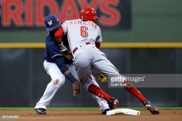Billy Hamilton of the Cincinnati Reds runs into Jonathan Villar of the Milwaukee Brewers while attempting to advance to third base in the first...