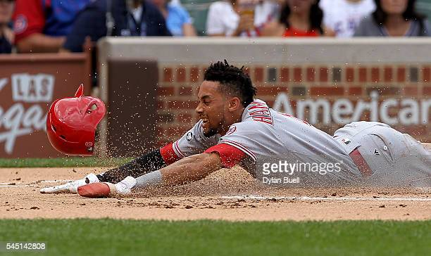 Billy Hamilton of the Cincinnati Reds slides into home plate to score a run in the first inning against the Chicago Cubs at Wrigley Field on July 5...