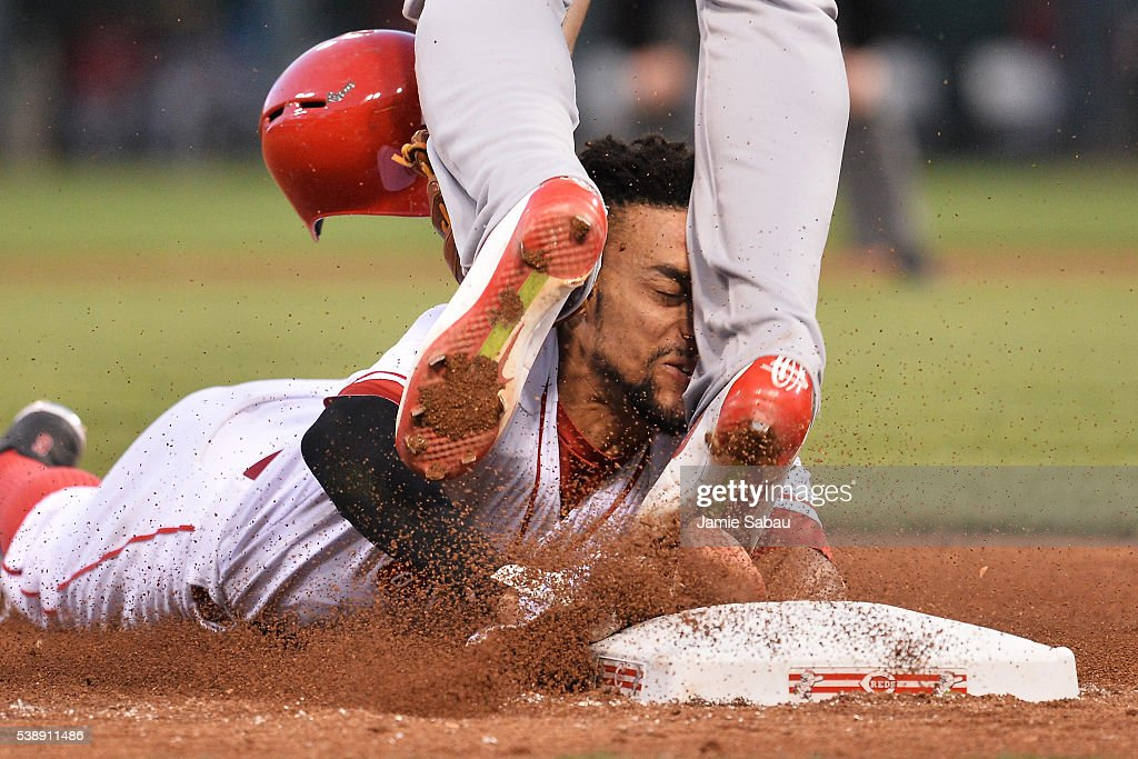 Billy Hamilton #6 of the Cincinnati Reds slides into the legs of Jhonny Peralta #27 of the St. Louis Cardinals while trying to steal third base in the fifth inning at Great American Ball Park on June 8, 2016 in Cincinnati, Ohio. Hamilton was called out as St. Louis defeated Cincinnati 12-7.