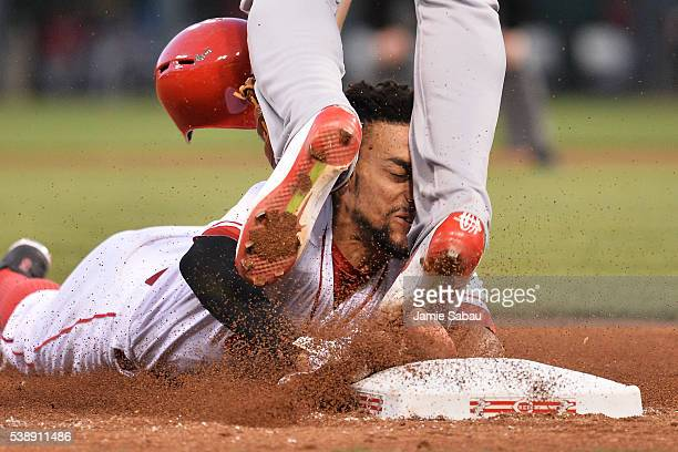 Billy Hamilton of the Cincinnati Reds slides into the legs of Jhonny Peralta of the St Louis Cardinals while trying to steal third base in the fifth...