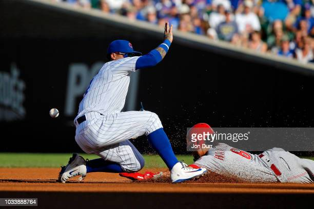 Billy Hamilton of the Cincinnati Reds steals second base as Javier Baez of the Chicago Cubs is unable to catch the throw during the sixth inning at...