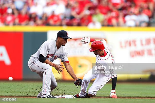 Billy Hamilton of the Cincinnati Reds steals second base as Xander Bogaerts of the Boston Red Sox lets the ball get past him in the first inning of...