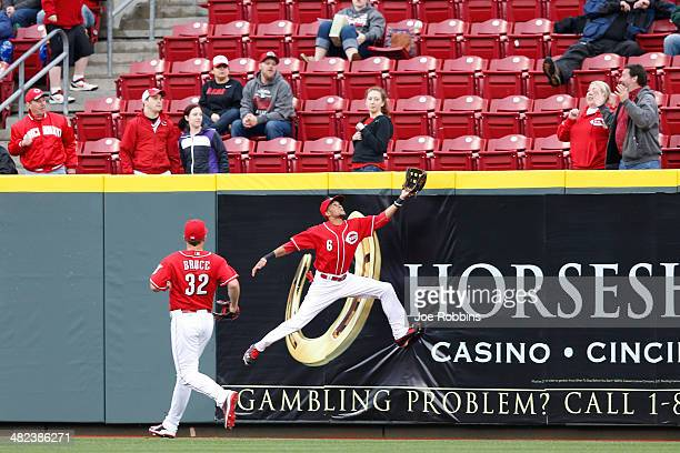 Billy Hamilton of the Cincinnati Reds tries but is unable to make a catch against the outfield wall in the seventh inning of the game against the St...