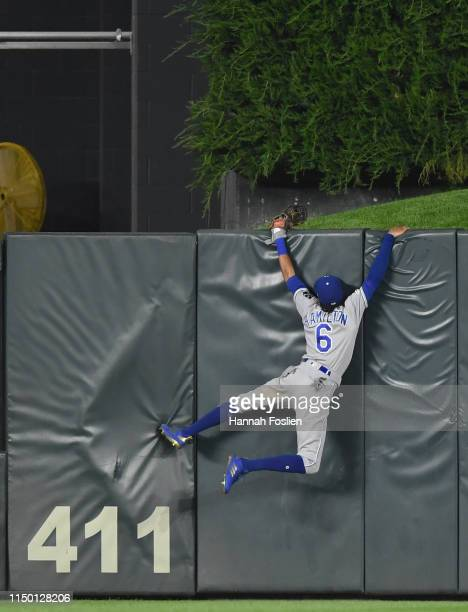 Billy Hamilton of the Kansas City Royals hangs on the center field wall after a two-run home run by Mitch Garver of the Minnesota Twins during the...