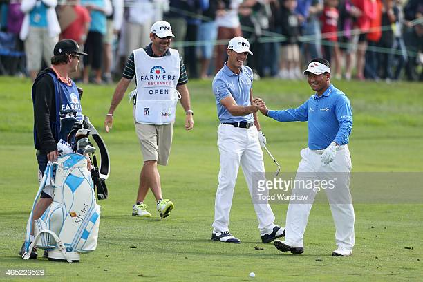 Billy Horschel is congratulated by KJ Choi after hitting a shot on the 18th fareway during the final round of the Farmers Insurance Open on Torrey...