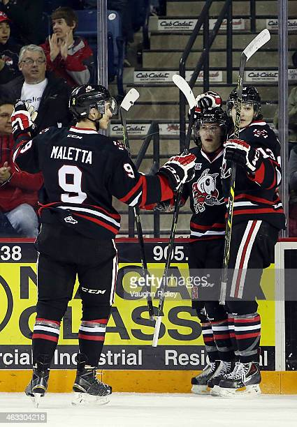 Billy Jenkins of the Niagara IceDogs celebrates a goal with Jordan Maletta and Graham Knott during an OHL game against the Mississauga Steelheads at...