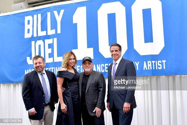 Billy Joel and wife Alexis Roderick MSG CEO and chairman James Dolan and New York Governor Andrew Cuomo pose in front of the banner at a press...