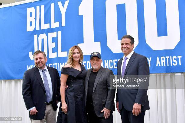 Billy Joel and wife Alexis Roderick MSG CEO and chairman James Dolan and New York Governor Andrew Cuomo pose in front of the banner honoring Joel's...