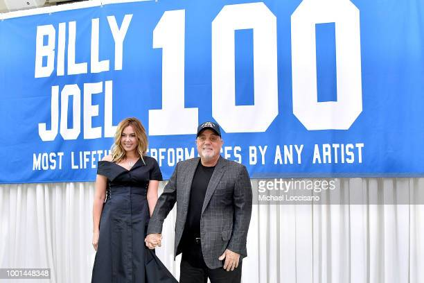 Billy Joel and wife Alexis Roderick pose in front of the banner during a press conference honoring Joel's 100th Lifetime Performance at Madison...